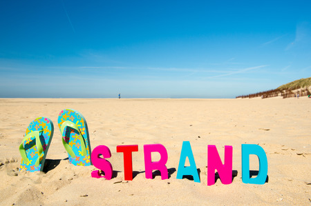 Dutch beach on wadden island Texel with the word strand and flip flops photo