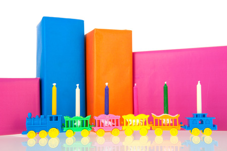 Colorful gifts with little train and birthday candles isolated over white background photo