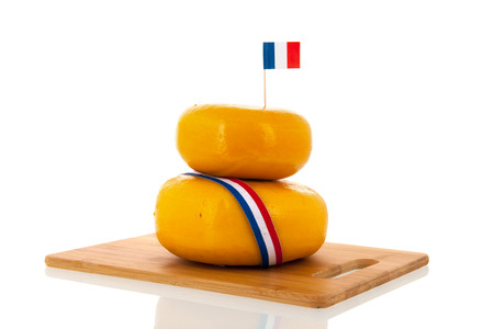 Two stacked whole French cheeses isolated over white background photo