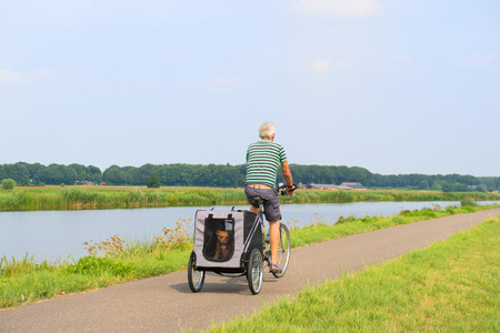 Senior man on bike with dog car riding near the river photo
