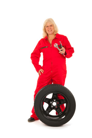Female car mechanic with wheel and tools isolated over white background photo