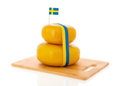 Two stacked whole Swedish cheeses isolated over white background photo