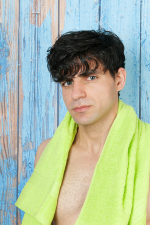 Young man in front of vintage wooden background with towel photo