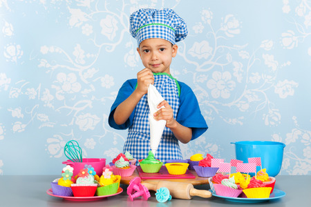 Little boy is baking colorful cupcakes with vintage wall paper in background photo