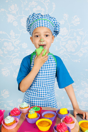 Little boy is tasting his self made colorful cupcakes with vintage wall paper in background photo