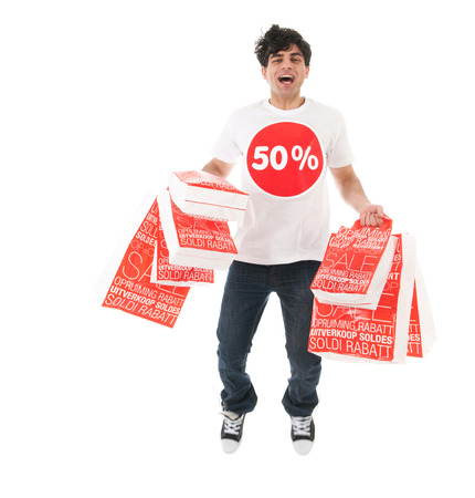 Young man is agitated and jumping high by the sale with many bags