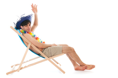 Young man with tropical hat sitting in beach chair photo