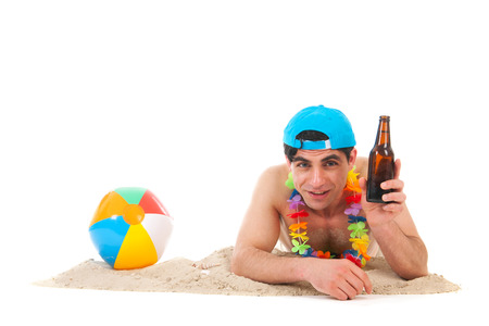 Young man laying at the beach drinking beer photo
