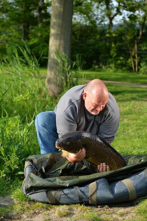 Proud fisherman with self captived carp photo