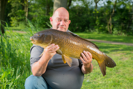 Proud fisherman with self captived carp photo