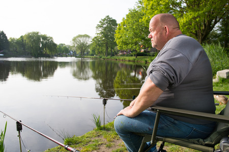 Fisherman sitting near lake with fishing rods photo
