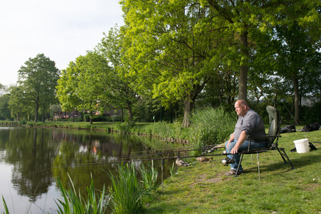 soest: Fisherman sitting near lake with fishing rods Stock Photo