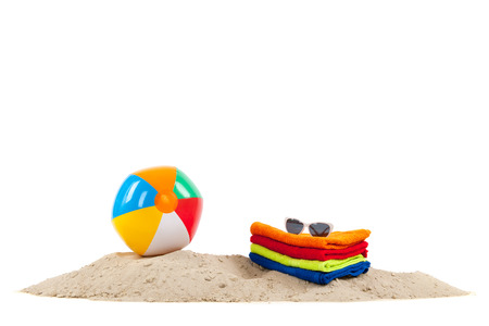 Beach ball and towels in sand isolated over white background photo