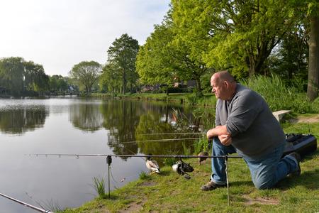 Fisherman sitting near lake with fishing rods photo