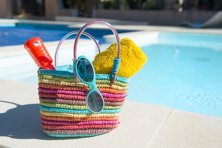 insolación: Vacaciones con bolsa de playa y toallas en la piscina
