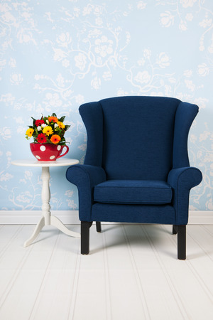 Interior blue living with vintage wall paper chair, table and flowers photo
