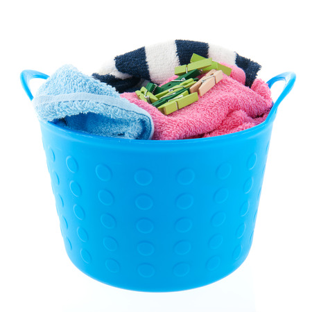 Full laundry basket with towels and clothes pins photo