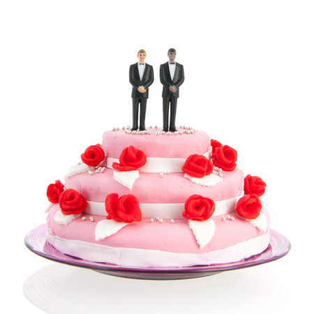 mixed gay couple on top of pink wedding cake with red roses isolated over white background