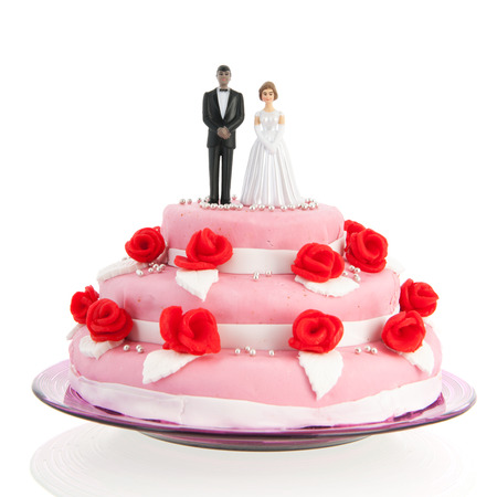 mixed couple on top of pink wedding cake with red roses isolated over white background photo