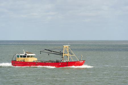 wadden sea: Red Dutch fishing trawler at wadden sea Stock Photo