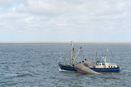 wadden: Blue Dutch fishing boat with nets at wadden sea