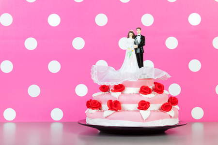Couple on top of pink wedding cake with red roses isolated over white background photo