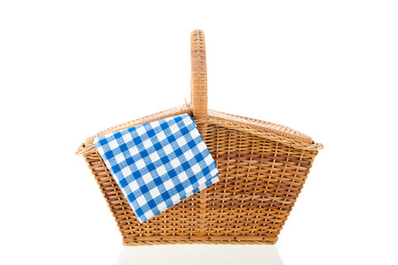 Picnic basket with blue checked napkin isolated over white background