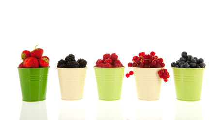 Row olorful green buckets with summer fruit isolated over white background