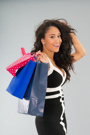 Young black woman with shopping bags on gray background photo