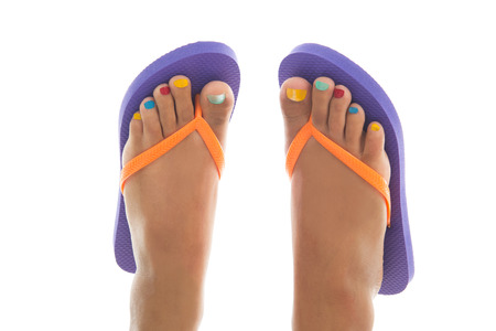 Black summer feet with colorful flip flops and toe nails photo