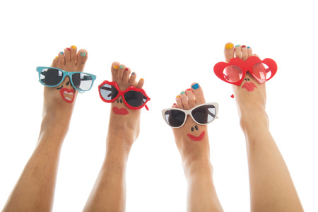 Happy and funny black and caucasian summer feet with colorful nail polish and sunglasses photo