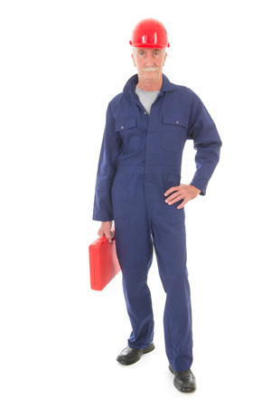studio happy overall: Senior laborer in blue work wear carrying a red suitcase isolated over white background Stock Photo