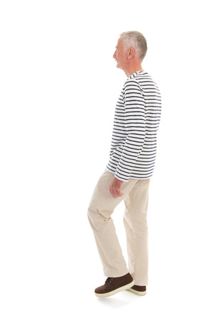 Senior man walking with full body in studio isolated over white background photo