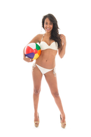 Black woman in bikini playing with colorful beach ball isolated over white background photo