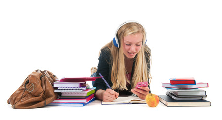 Teen girl with distraction bij the cell phone while making homework for school
