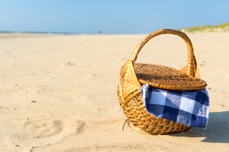 picnic cloth: Picnic basket with blue checked cloth at the beach Stock Photo