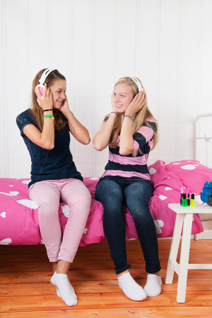 Two teenager girls listening to music with headphones photo