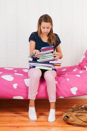 too many: Fourteen year old girl with many schoolbooks and too many homework