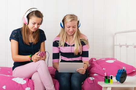 Two teenager girls listening to tablet and smartphone photo