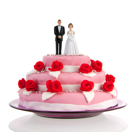 Pink wedding cake with red roses and couple on top photo