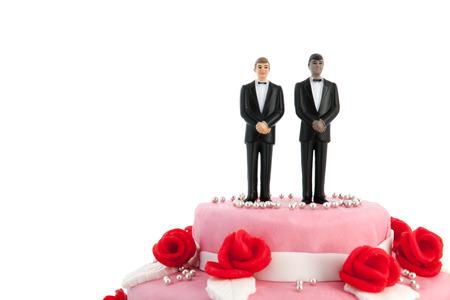 Roze bruidstaart met rode rozen en paar op de top Stockfoto