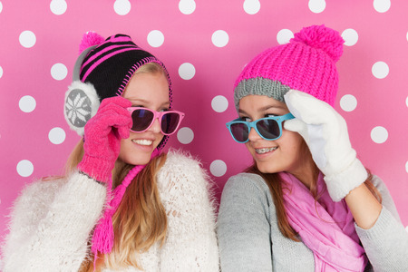 warmers: Two fourteen years old teens as girlfriends in winter Stock Photo