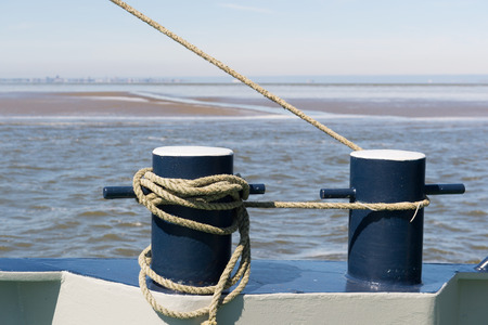 Bollards on ship with ropes at the sea