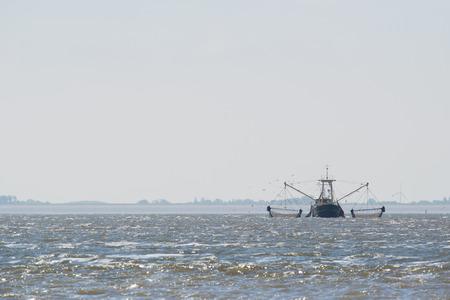 wadden sea: fishing boat with nets on Dutch wadden sea