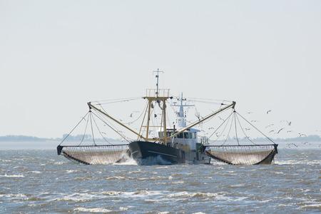wadden: fishing boat with nets on Dutch wadden sea