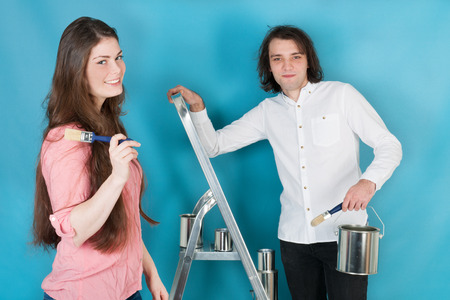 refurbishing: Young couple with paint and brushes in interior