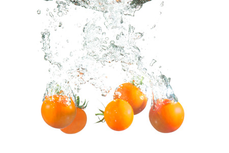 Many tomatoes washing in water with splash photo