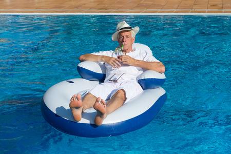 rijke man ontspannen in een eigen zwembad