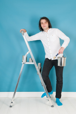 stepladder: Young man with paint and brushes on stepladder in interior