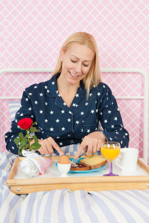 mother'sday: Woman of mature age eating breakfast on bed Stock Photo